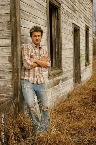 Man Leaning Against A Farm Structure