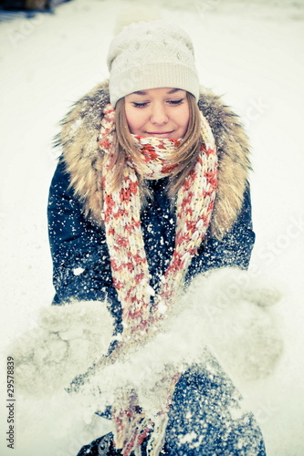 Happy young woman plays with a snow