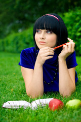 Young beautiful woman lays on green field with apple and book