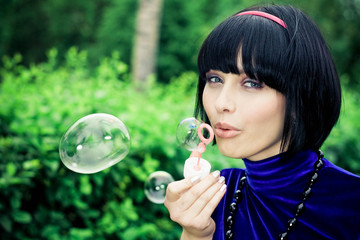 young female makes soap bubbles