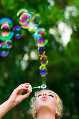 Young beautiful woman blowing soap bubbles