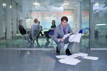 Businessman picking up documents in front of conference room