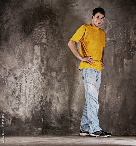 Young happy man against grunge wall