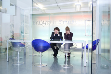 Two sad businesspeople in conference room