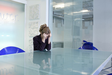 Young businesswoman in conference room crying
