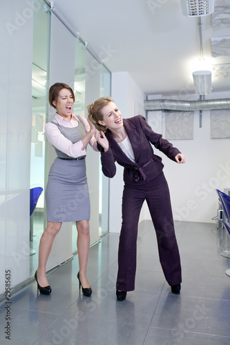 Two businesswomen fighting in office