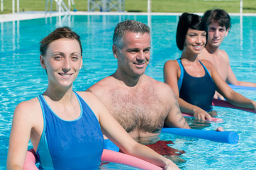 Smiling fitness people exercising in swimming pool