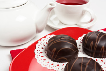 Delicious three chocolate cake on red plate with tea cup