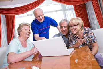 Seniors watching photos via laptop