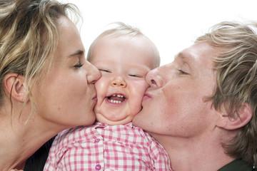 Portrait d'un couple embrassant leur bébé joufflu
