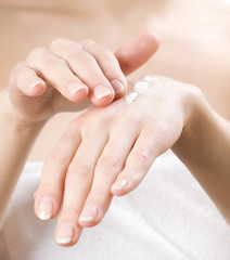 Female applying moisturizer to her Hands