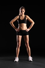 Fit young woman standing in black sports outfit
