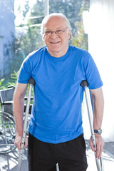 Happy senior man with crutches