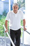 Close up of senior patient walking with hand on railing