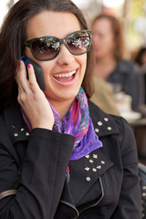 Pretty young woman speaking on a mobile phone in a cafe