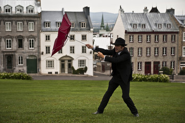 Businessman Struggles with Umbrella