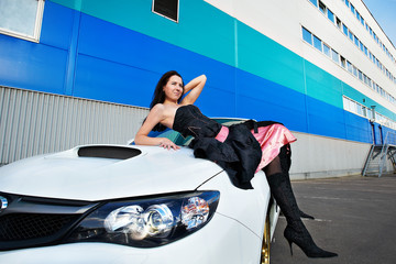 Young woman on hood of a white sports car