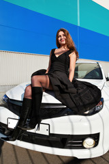 Sexy babe on the hood of a white sports car