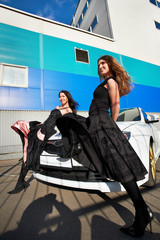 Two beautiful young woman and stylish white sports car