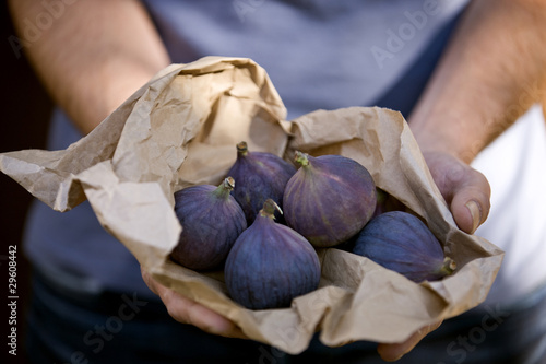 A man holding a paper bag containing fresh figs