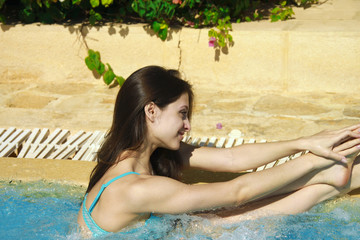 Relaxing beautiful girl in bikini having a rest in blue jacuzzi