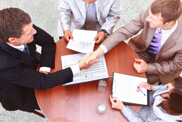 handshake over paper and pen,blurry computer in the