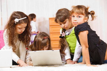Kids sit around laptop