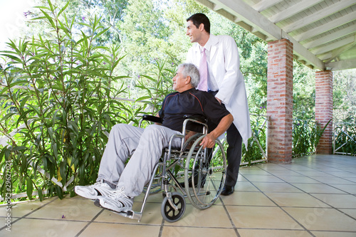 Doctor assisting a man on a wheelchair