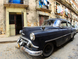 A classic old car is black color parked in front of the building