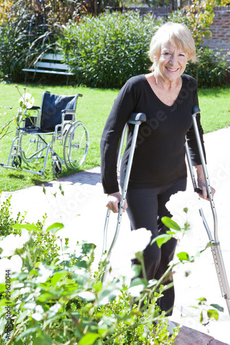 Mature woman walking in the garden with crutches