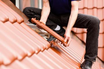 Dachdecker deckt Dach mit Dachziegel ein