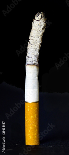 Lit standing cigarette isolated on black background
