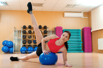 Young woman doing fitness exercises with sport ball