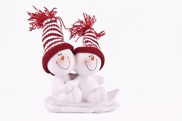 Two snowmen in red hats skating