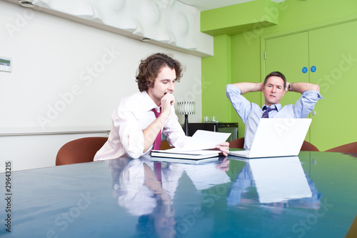Two serious businessmen working in conference room