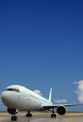 Airplane on airport. Blue sky background.