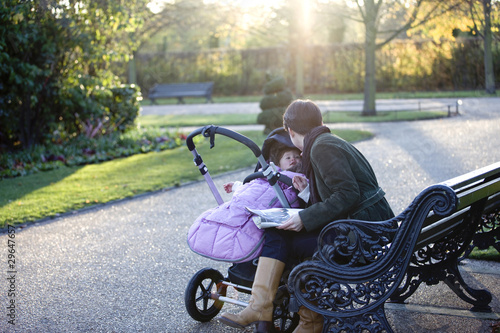 A mother sitting on a bench, looking at her daughter in a buggy