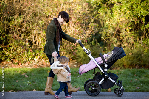 A mother walking with her baby girl in the park