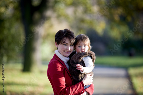 A mother holding her baby girl in the park