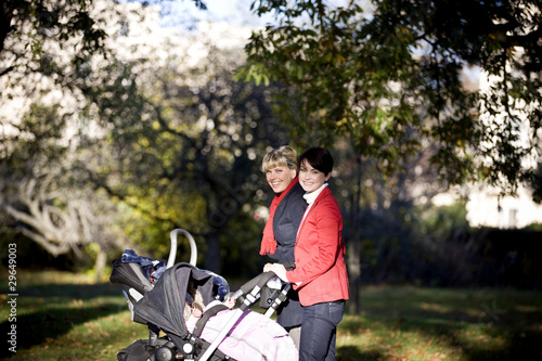 Two mothers pushing their buggies in the park, smiling