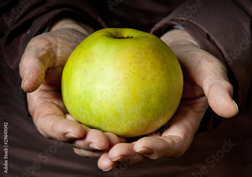 Senior Woman Holding Apple in her Palms.