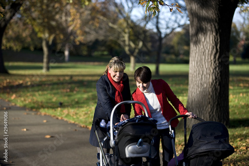 Two mothers looking at their babies in buggies in the park