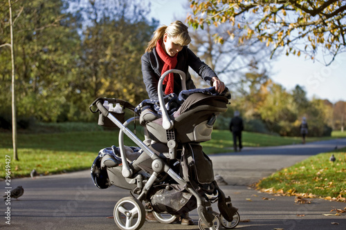 A mother looking at her babies in a buggy in the park