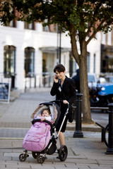 A mother standing with a buggy, talking on her mobile phone