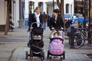 Two mothers pushing their buggies in the street