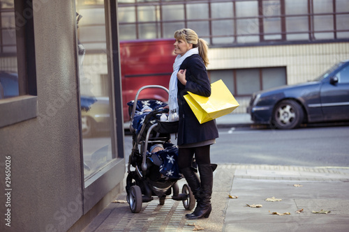 A mother pushing a buggy, looking in a shop window