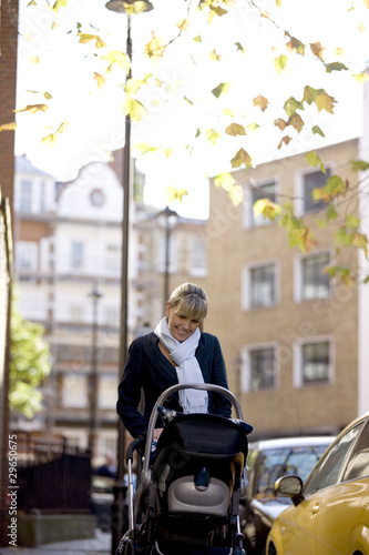 A mother pushing a buggy in the street