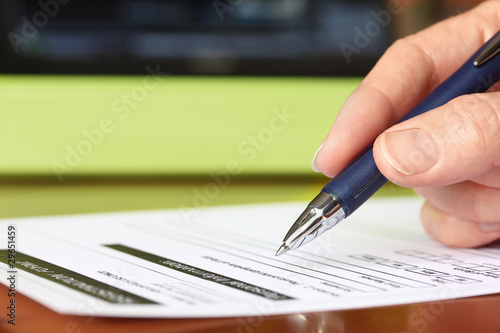 Hand with Pen Signing Form by Green Folder