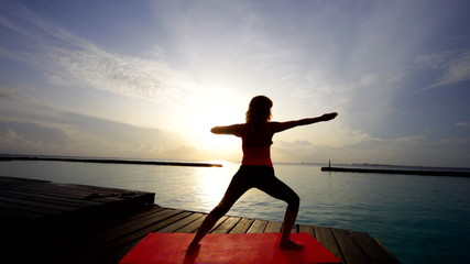 woman practices yoga at sunset