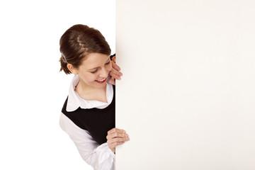 Junge Frau lacht und blickt auf leere Werbetafel